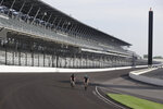 IndyCar driver Charlie Kimball and Dalton Kellett ride their bicycles into turn one at Indianapolis Motor Speedway, Sunday, May 24, 2020, in Indianapolis. The Indianapolis 500 was postponed because of the coronavirus pandemic. The race will instead be held Aug. 23, three months later than its May 24 scheduled date. (AP Photo/Darron Cummings)