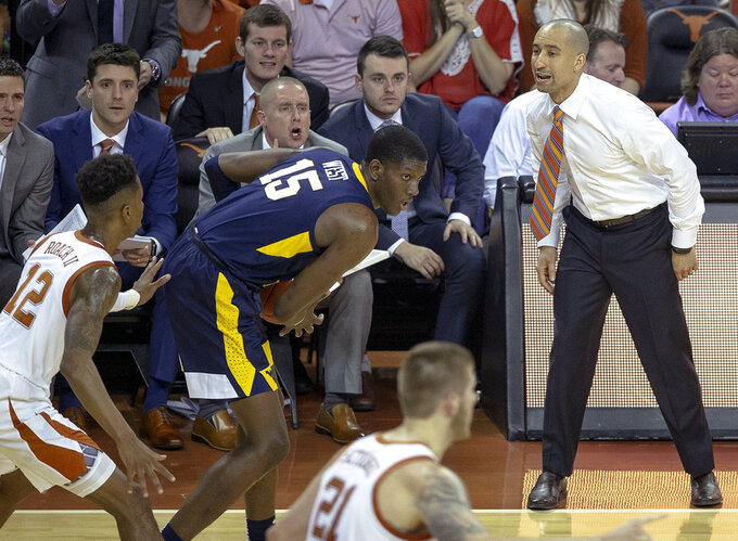 Texas head coach Shaka Smart shouts to guard Kerwin Roach II (12) as West Virginia forward Lamont West (15) controls the ball during an NCAA college basketball game on Saturday, Jan. 5, 2019, in Austin, Texas. (Nick Wagner/Austin American-Statesman via AP)