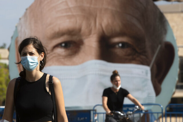 An Israeli woman walks past a banner encouraging people to wear face masks in Tel Aviv, Israel, Thursday, Sept. 24, 2020. Israeli Prime Minister Benjamin Netanyahu on Wednesday announced plans for a strict, two-week nationwide lockdown in a bid to slow a raging coronavirus outbreak. (AP Photo/Sebastian Scheiner)