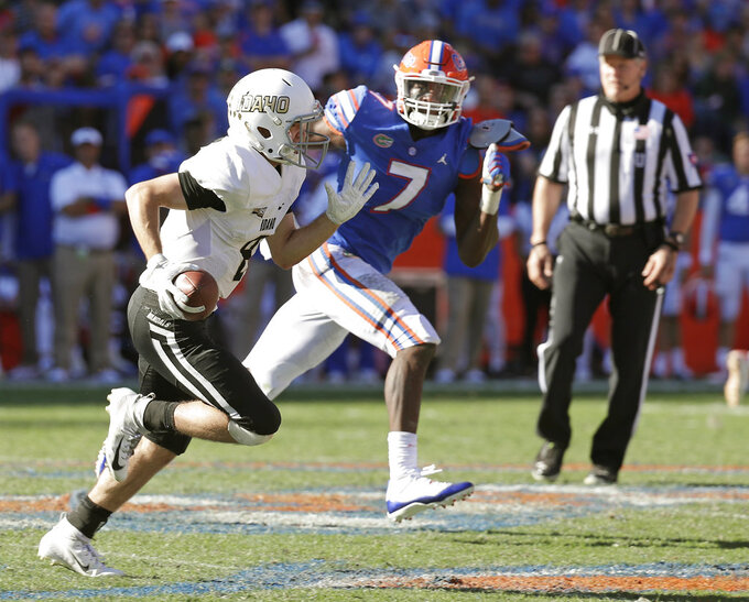 Idaho quarterback Mason Petrino scrambles out of the pocket as he is pressured by Florida linebacker Jeremiah Moon (7) during the second half of an NCAA college football game, Saturday, Nov. 17, 2018, in Gainesville, Fla. (AP Photo/John Raoux)