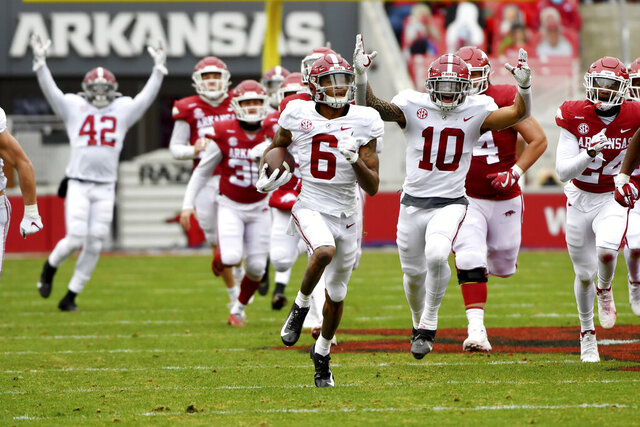 Alabama's DeVonta Smith (6) returns a punt for a touchdown against Arkansas during the first half of an NCAA college football game Saturday, Dec. 12, 2020, in Fayetteville, Ark. DeVonta Smith is The Associated Press college football player of the year, becoming the first wide receiver to win the award since it was established in 1998, Tuesday, Dec. 29, 2020.(AP Photo/Michael Woods)