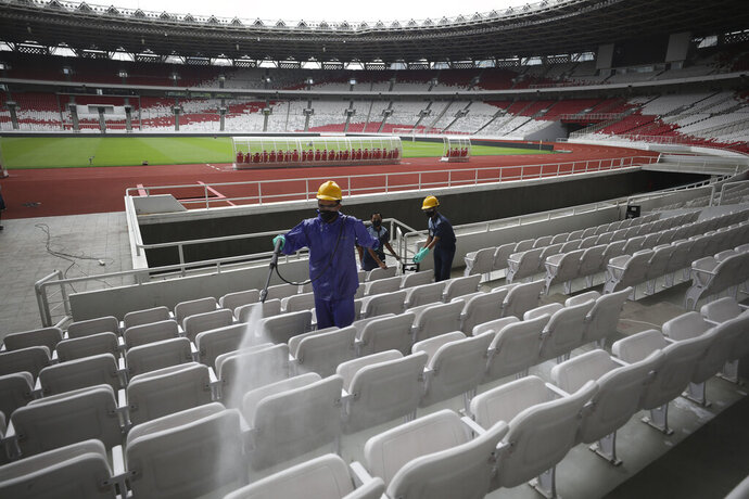 Workers spray disinfectant over spectator seats at the Gelora Bung Karno Main Stadium in efforts to curb the spread of the coronavirus outbreak, in Jakarta, Indonesia, Thursday, March 26, 2020. The new coronavirus causes mild or moderate symptoms for most people, but for some, especially older adults and people with existing health problems, it can cause more severe illness or death. (AP Photo/Dita Alangkara)