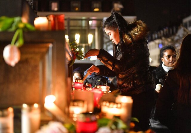 A woman lights a candle at a monument on the market place during a mourning for the victims of the shooting in Hanau, Germany, Thursday, Feb. 20, 2020. A 43-year-old German man shot and killed nine people at several locations in a Frankfurt suburb overnight in attacks that appear to have been motivated by far-right beliefs, officials said Thursday. (AP Photo/Martin Meissner)