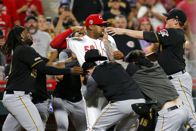 Cincinnati Reds relief pitcher Amir Garrett (50) looks to throw a punch as he is held back by a number of Pittsburgh Pirates players during a brawl in the ninth inning of a baseball game in Cincinnati, July 30, 2019. (Sam Greene/The Cincinnati Enquirer via AP)