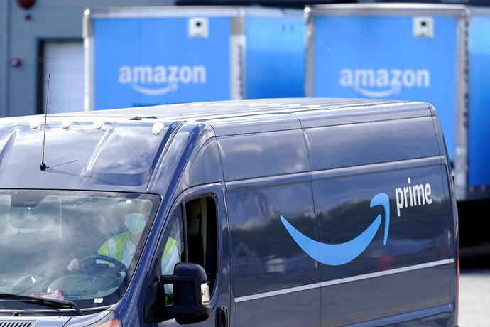 FILE - In this Oct. 1, 2020 file photo, an Amazon Prime logo appears on the side of a delivery van as it departs an Amazon Warehouse location in Dedham, Mass.  Online shopping has been a lifeline for many as the virus pandemic shuttered stores and kept people at home. The COVID-19 pandemic has accelerated the change in how people shop in a world growing more comfortable and savvier with technology.  (AP Photo/Steven Senne, File)