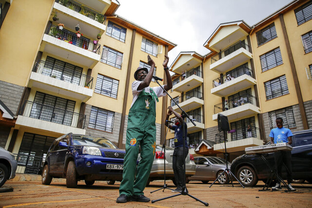 Rev. Paul Machira preaches and sings to residents in an apartment block in Nairobi, Kenya, Sunday, May 17, 2020. The Kenyan pastor has taken his church service for children on the road due to coronavirus restrictions and preaches from parking lots outside apartment buildings while kids and their parents dance on balconies above. (AP Photo/Brian Inganga)