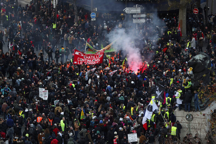 Protesters march during a demonstration Tuesday, Dec. 10, 2019 in Paris. French airport employees, teachers and other workers joined nationwide strikes Tuesday as unions cranked up pressure on the government to scrap upcoming changes to the country's national retirement system. (AP Photo/Thibault Camus)