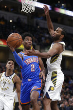 Oklahoma City Thunder guard Shai Gilgeous-Alexander (2) makes a pass around Indiana Pacers forward T.J. Warren during the first half of an NBA basketball game in Indianapolis, Tuesday, Nov. 12, 2019. (AP Photo/Michael Conroy)