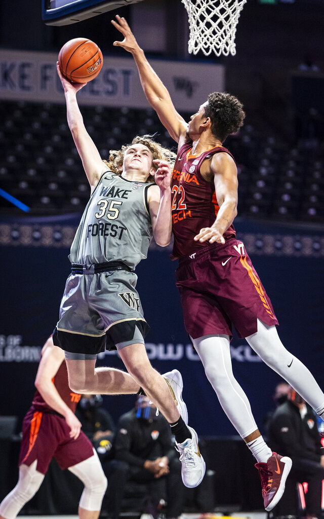Wake Forest guard Carter Whitt (35) shoots under defense from Virginia Tech forward Keve Aluma (22) during an NCAA college basketball game Sunday, Jan. 17, 2021, in Winston-Salem, N.C. (Andrew Dye/The Winston-Salem Journal via AP)
