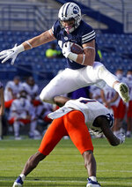 FILE - BYU tight end Masen Wake (13) hurdles UTSA safety Antonio Parks (4) in the second half during an NCAA college football game Saturday, Oct. 10, 2020, in Provo, Utah. The play was called back after an offensive holding call. BYU walk-on fullback/tight end Masen Wake lost his mom to cancer when he was 8 years old. He honors her by writing