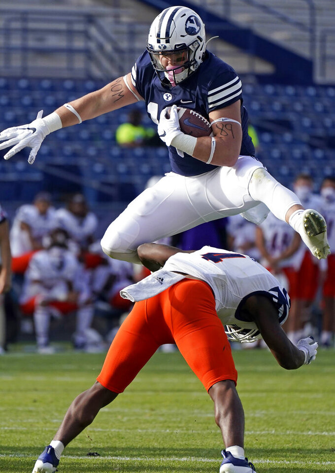 "FILE - BYU tight end Masen Wake (13) hurdles UTSA safety Antonio Parks (4) in the second half during an NCAA college football game Saturday, Oct. 10, 2020, in Provo, Utah. The play was called back after an offensive holding call. BYU walk-on fullback/tight end Masen Wake lost his mom to cancer when he was 8 years old. He honors her by writing ""Mom"" on the inside of both cleats and across his bicep. (AP Photo/Rick Bowmer, Pool)"