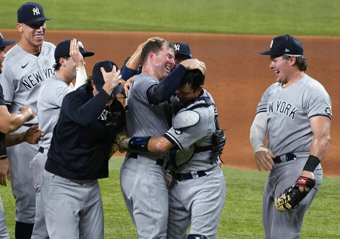 New York Yankees starting pitcher Corey Kluber, third from right, celebrates with catcher Kyle Higashioka, second from right, and the rest of the team after throwing a no-hitter against the Texas Rangers in a baseball game in Arlington, Texas, Wednesday, May 19, 2021. (AP Photo/Tony Gutierrez)