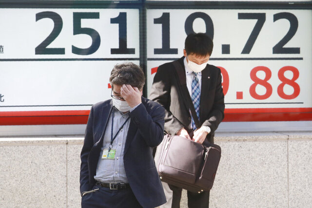 People walk by an electronic stock board of a securities firm in Tokyo, Tuesday, Nov. 10, 2020. Asian stock markets rose for second day Tuesday on hopes for progress toward a possible coronavirus vaccine that might allow the world to revive manufacturing, shopping and normal life. (AP Photo/Koji Sasahara)