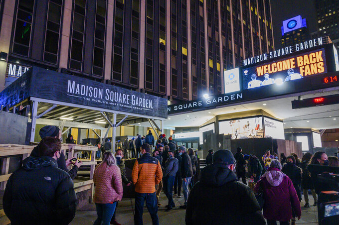 Fans line up outside Madison Square Garden for an NBA basketball game between the New York Knicks and the Golden State Warriors in New York on Tuesday, Feb. 23, 2021. (AP Photo/Brittainy Newman)