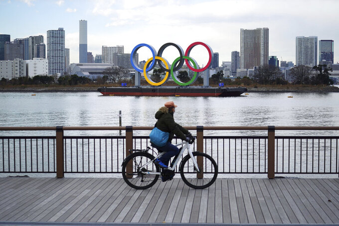"A man rides a bicycle near the Olympic rings floating in the water in the Odaiba section Friday, Jan. 8, 2021 in Tokyo. The senior member of the International Olympic Committee has said he ""can't be certain""the postponed Tokyo Olympics will open in just over six months because of the surging pandemic in Japan and elsewhere. (AP Photo/Eugene Hoshiko)"