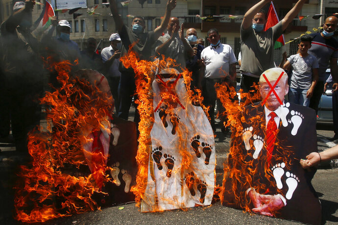 FILE - In this Aug. 14, 2020 file photo, Palestinians burn pictures of U.S. President Donald Trump, Abu Dhabi Crown Prince Mohammed bin Zayed al-Nahyan and and Israeli Prime Minister Benjamin Netanyahu during a protest against the United Arab Emirates' deal with Israel, in the West Bank city of Nablus.  For the first time in more than a quarter-century, a U.S. president will host a signing ceremony, Tuesday, Aug. 15,  between Israelis and Arabs at the White House, billing it as an