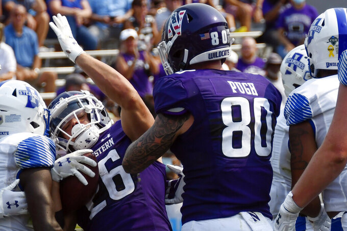 Northwestern running back Evan Hull (26) celebrates with tight end Trey Pugh (80) after scoring a touchdown against Indiana State during the second half of an NCAA college football game in Evanston, Ill., Saturday, Sept. 11, 2021. (AP Photo/Matt Marton)