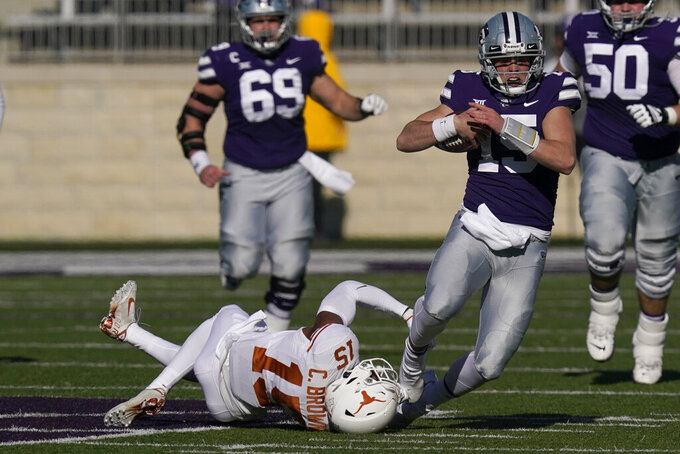 Kansas State quarterback Will Howard, right, is tackled by Texas defensive back Chris Brown, left, during the first half of an NCAA college football game in Manhattan, Kan., Saturday, Dec. 5, 2020. (AP Photo/Orlin Wagner)