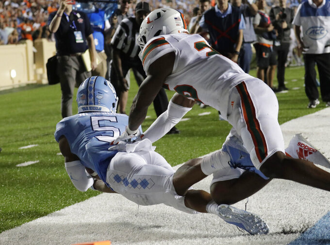 North Carolina's Dazz Newsome (5) hauls in a touchdown pass against Miami's Gurvan Hall Jr. during the fourth quarter of an NCAA college football game in Chapel Hill, N.C., Saturday, Sept. 7, 2019. (AP Photo/Chris Seward)