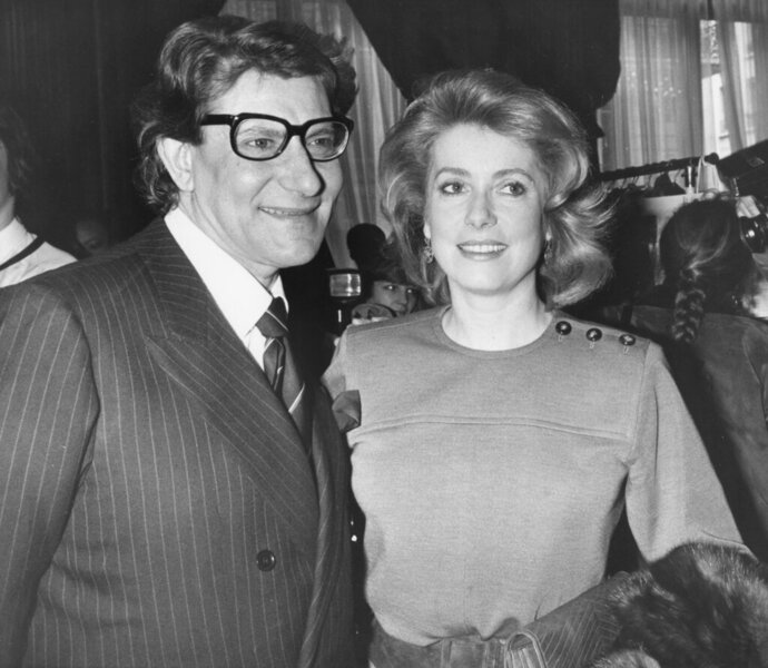 FILE - In this Jan. 30 1985 file photo, French actress Catherine Deneuve congratulates French fashion designer Yves Saint Laurent after the presentation of spring-summer haute couture collection in Paris. Denueve's family said in a statement released Wednesday Nov. 6, 2019, that the 76-year-old actress suffered a