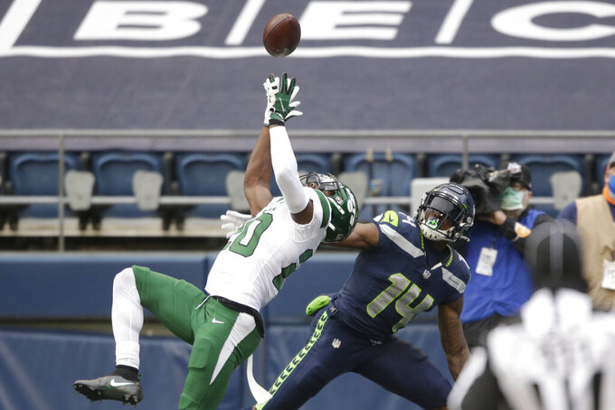 New York Jets' safety Marcus Maye (20) intercepts a pass intended for Seattle Seahawks wide receiver DK Metcalf (14) during the first half of an NFL football game, Sunday, Dec. 13, 2020, in Seattle. (AP Photo/Lindsey Wasson)