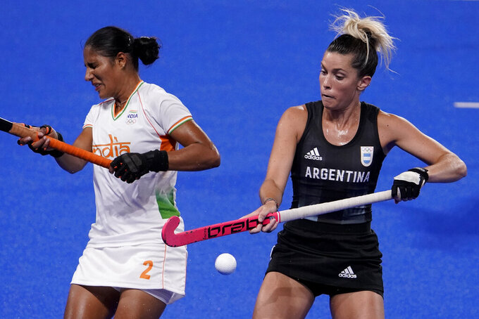 La argentina Agustina Albertarrio, a la derecha, y Gurjit Kaur, de la India, a la izquierda, reaccionan a una pelota suelta durante un partido por las semifinales del hockey sobre césped femenino en los Juegos Olímpicos de Verano 2020, en Tokio, Japón, el miércoles 4 de agosto del 2021.(Foto AP/John Locher)