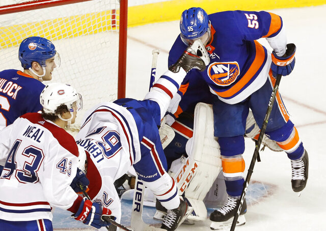 New York Islanders defenseman Johnny Boychuk (55) takes a skate to the face as Montreal Canadiens left wing Artturi Lehkonen (62) falls to the ice in front of the goal during the third period of an NHL hockey game, Tuesday, March 3, 2020, in New York. Islanders defenseman Ryan Pulock (6) and Canadiens center Jordan Weal (43) are nearby. (AP Photo/Kathy Willens)