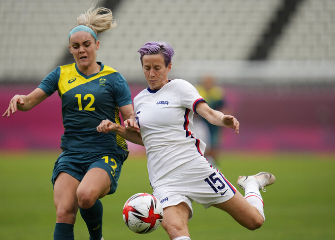 United States' Megan Rapinoe, right, and Australia's Ellie Carpenter battle for the ball during a women's soccer match at the 2020 Summer Olympics, Tuesday, July 27, 2021, in Kashima, Japan. (AP Photo/Fernando Vergara)