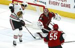 Arizona Coyotes goaltender Darcy Kuemper (35) makes a save as Chicago Blackhawks center Dylan Strome (17) looks for a rebound as Coyotes defenseman Jason Demers (55) looks on during the second period of an NHL hockey game Tuesday, March 26, 2019, in Glendale, Ariz. (AP Photo/Ross D. Franklin)