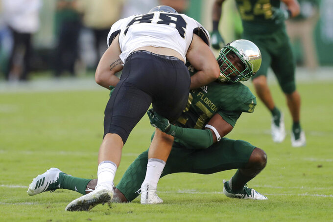 Central Florida's Jake Hescock runs through the tackle of South Florida's Naytron Culpepper during the first half of an NCAA college football game Friday, Nov. 23, 2018, in Tampa, Fla. (AP Photo/Mike Carlson)