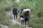 A Colombian police officer detains two smugglers who crossed the border illegally in La Parada, on the outskirts of Cucuta, Colombia, on the border with Venezuela, Tuesday, Feb. 5, 2019. Venezuelan opposition leader Juan Guaido is moving ahead with plans to try to bring in humanitarian aid through the Colombian border city of Cucuta, where the U.S. government will transport and store food and medical supplies destined for Venezuela. (AP Photo/Fernando Vergara)