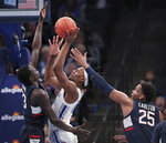 Memphis forward Precious Achiuwa (55) shoots under pressure from Connecticut's Akok Akok, left, and Josh Carlton (25) during an NCAA college basketball game, Saturday, Feb. 1 2020, at the FedExForum in Memphis, Tenn. (Jim Weber/Daily Memphian via AP)