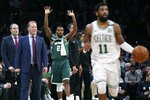 Milwaukee Bucks' Sterling Brown (23) reacts beside head coach Mike Budenholzer, second from left, as Boston Celtics' Kyrie Irving (11) brings the ball upcourt during the second half of Game 4 of a second-round NBA basketball playoff series in Boston, Monday, May 6, 2019. (AP Photo/Michael Dwyer)
