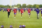 Minnesota Vikings quarterbacks Danny Etling (6), Nate Stanley (14), Kirk Cousins (8) and Jake Browning jog during the NFL football team's training camp, Thursday, Aug. 5, 2021, in Eagan, Minn. (AP Photo/Jim Mone)