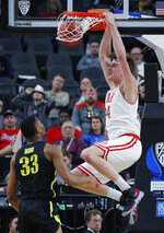 Utah's Jayce Johnson dunks over Oregon's Francis Okoro during the second half of an NCAA college basketball game in the quarterfinals of the Pac-12 men's tournament Thursday, March 14, 2019, in Las Vegas. (AP Photo/John Locher)