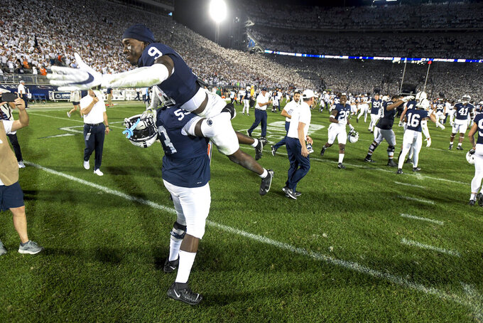 Penn State offensive lineman Rasheed Walker (53) lifts cornerback Joey Porter Jr. (9 while celebrating a 28-20 victory over Auburn after an NCAA college football game in State College, Pa., on Saturday, Sept. 18, 2021. (AP Photo/Barry Reeger)