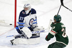 Winnipeg Jets goalie Connor Hellecuyck (37) watches a goal by the Minnesota Wild in the third period as Minnesota Wild defenseman Matt Dumba (24) skates by in the third period of an NHL hockey game Saturday, Jan. 4, 2020, in St. Paul, Minn. The Wild defeated the Jets 3-2. (AP Photo/Andy Clayton-King)