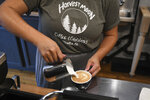 Teen worker Courtney Collins, 19, pours a drink at Harvest Moon Coffee & Chocolates in Tarentum, Pa. on Friday, July 16, 2021. (Kristina Serafini/Pittsburgh Tribune-Review via AP)