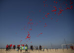 Red balloons are released to honor the victims of COVID-19 in a demonstration organized by Rio de Paz, on Copacabana beach in Rio de Janeiro, Brazil, Saturday, Aug. 8, 2020, as the country heads to a milestone of 100,000 new coronavirus related deaths. (AP Photo/Silvia Izquierdo)