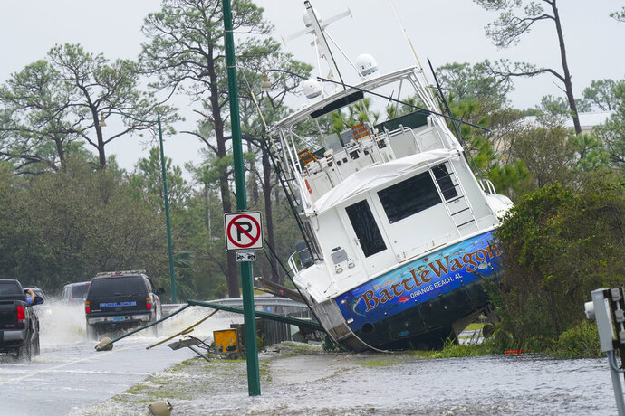 A boat is washed up near a road after Hurricane Sally moved through the area, Wednesday, Sept. 16, 2020, in Orange Beach, Ala. Hurricane Sally made landfall Wednesday near Gulf Shores, Alabama, as a Category 2 storm, pushing a surge of ocean water onto the coast and dumping torrential rain that forecasters said would cause dangerous flooding from the Florida Panhandle to Mississippi and well inland in the days ahead. (AP Photo/Gerald Herbert)