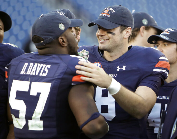 Auburn quarterback Jarrett Stidham (8) celebrates with linebacker Deshaun Davis (57) after the Music City Bowl NCAA college football game against Purdue, Friday, Dec. 28, 2018, in Nashville, Tenn. Stidham threw for 373 yards and five touchdowns in his final college game as Auburn routed Purdue 63-14. (AP Photo/Mark Humphrey)