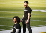 Free agent quarterback Colin Kaepernick, left, laughs will stretching before a workout for NFL football scouts and media, Saturday, Nov. 16, 2019, in Riverdale, Ga. (AP Photo/Todd Kirkland)