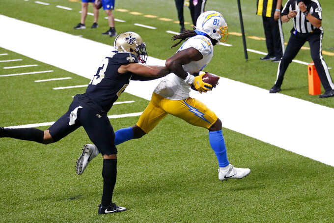 Los Angeles Chargers wide receiver Mike Williams (81) pulls in a touchdown reception as New Orleans Saints cornerback Marshon Lattimore (23) covers in the first half of an NFL football game in New Orleans, Monday, Oct. 12, 2020. (AP Photo/Brett Duke)