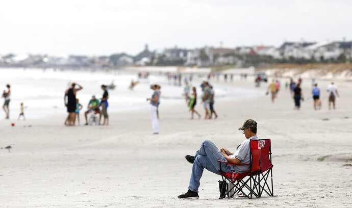 FILE - In this Sept. 13, 2018, file photo, beach goers hang out at the Isle of Palms, S.C., as Hurricane Florence spins out in the Atlantic ocean. Conservation groups suing President Donald Trump's administration over plans to conduct offshore drilling tests want a judge to halt preparatory work for the drilling until their case is heard in court. A motion filed Wednesday, Feb. 20, 2019, in federal court in South Carolina seeks an injunction to stop testing involving seismic air guns. The lawsuit the conservation groups and cities along South Carolina's coast filed seeks to permanently halt the offshore drilling tests.  (AP Photo/Mic Smith, File)