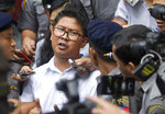 """FILE - In this Sept. 3, 2018 file photo, Reuters journalist Wa Lone, center, talks to journalists while he is escorted by polices as they leave the court in Yangon, Myanmar. A Myanmar court sentenced two Reuters journalists  to seven years in prison  for illegal possession of official documents. More than a dozen global news organizations including The Associated Press have formed a coalition to spotlight the world's most threatened journalists. Member editors and publishers of the One Free Press Coalition will publish across platforms each month a """"10 Most Urgent"""" list of journalists whose press freedoms are being abused. (AP Photo/Thein Zaw)"""