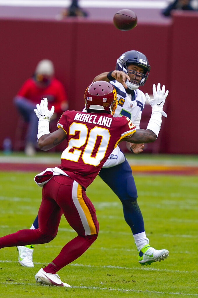Seattle Seahawks quarterback Russell Wilson (3) passes the ball under pressure from Washington Football Team cornerback Jimmy Moreland (20) during the first half of an NFL football game, Sunday, Dec. 20, 2020, in Landover, Md. (AP Photo/Susan Walsh)