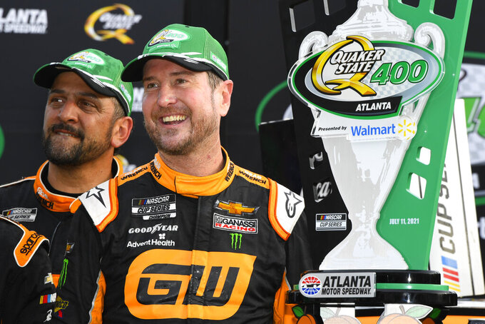Kurt Busch stands in Victory Lane with the trophy after winning a NASCAR Cup Series auto race, Sunday, July, 11, 2021, in Hampton, Ga. (AP Photo/John Amis)
