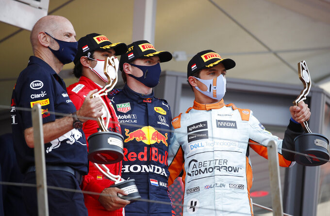 First place Red Bull driver Max Verstappen of the Netherlands, center, second place Ferrari driver Carlos Sainz of Spain, second left, and third place Mclaren driver Lando Norris of Britain, right, celebrate with their trophies on the podium during the Monaco Grand Prix at the Monaco racetrack, in Monaco, Sunday, May 23, 2021. (Sebastien Nogier, Pool via AP)