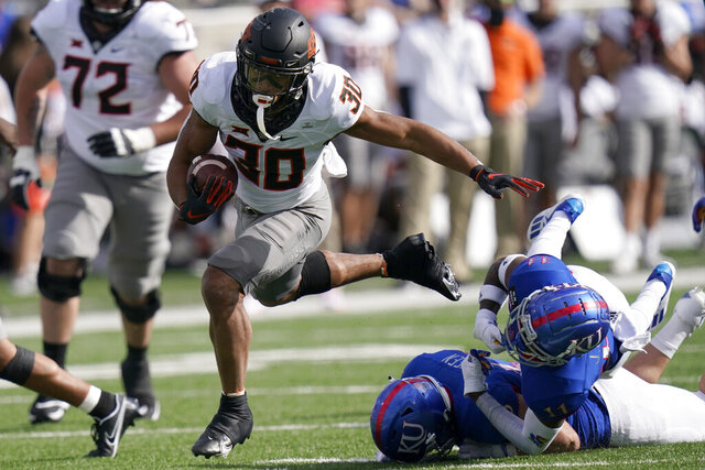 Oklahoma State running back Chuba Hubbard (30) breaks away from Kansas cornerback Johnquai Lewis (11) during the first half of an NCAA college football game in Lawrence, Kan., Saturday, Oct. 3, 2020. (AP Photo/Orlin Wagner)