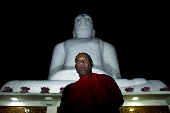 """In this Thursday, Nov. 14, 2019, photo, Yatawatte Dhammananda, a monk and Bodu Bala Sena organizer, stands for a photograph outside a Buddhist temple in Kandy, Sri Lanka. In Myanmar, like Sri Lanka, there is a view among nationalists that Muslims are an existential threat to their faith and way of life, despite Buddhists being the overwhelming majority. """"They have the intention of making this a Muslim country. They are working toward that, but we can't let that happen,"""" said Yatawatte. (AP Photo/Dar Yasin)"""